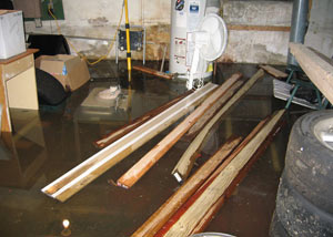 A severely flooding basement with lumber and personal items floating in a foot of water